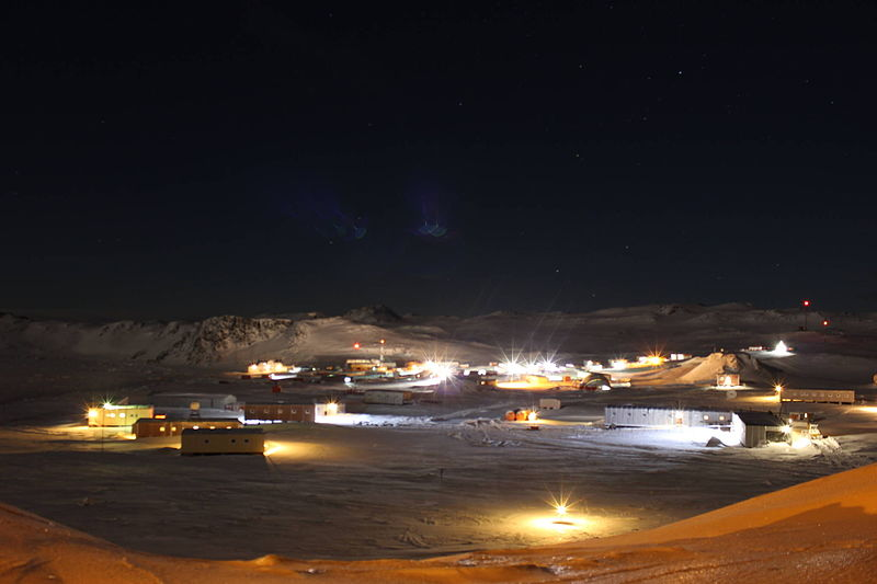 Multiple low buildings on a snowy plain, with snow-covered mountains in the background, under a black night sky.