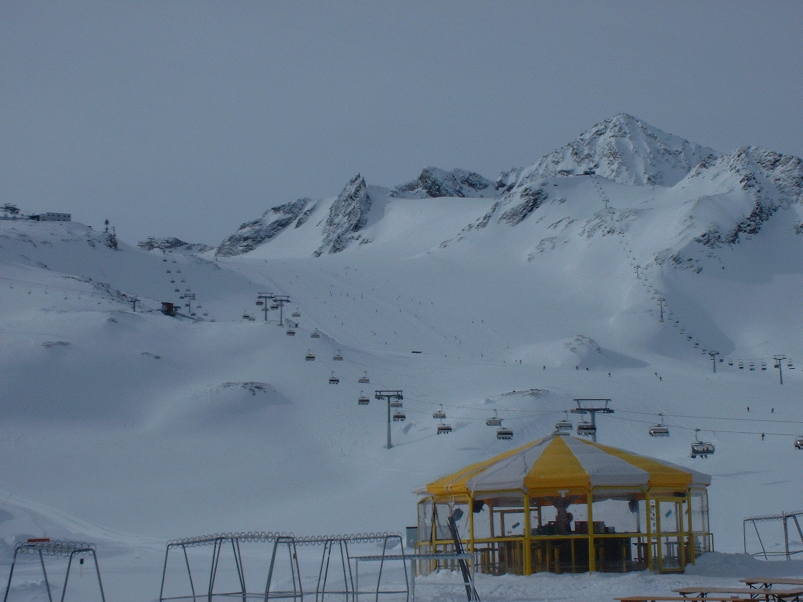 Two mountains, covered in snow, under a cloudy grey sky. Two ski lifts run up towards them. In the foreground is a glass-walled gazebo with a yellow roof.