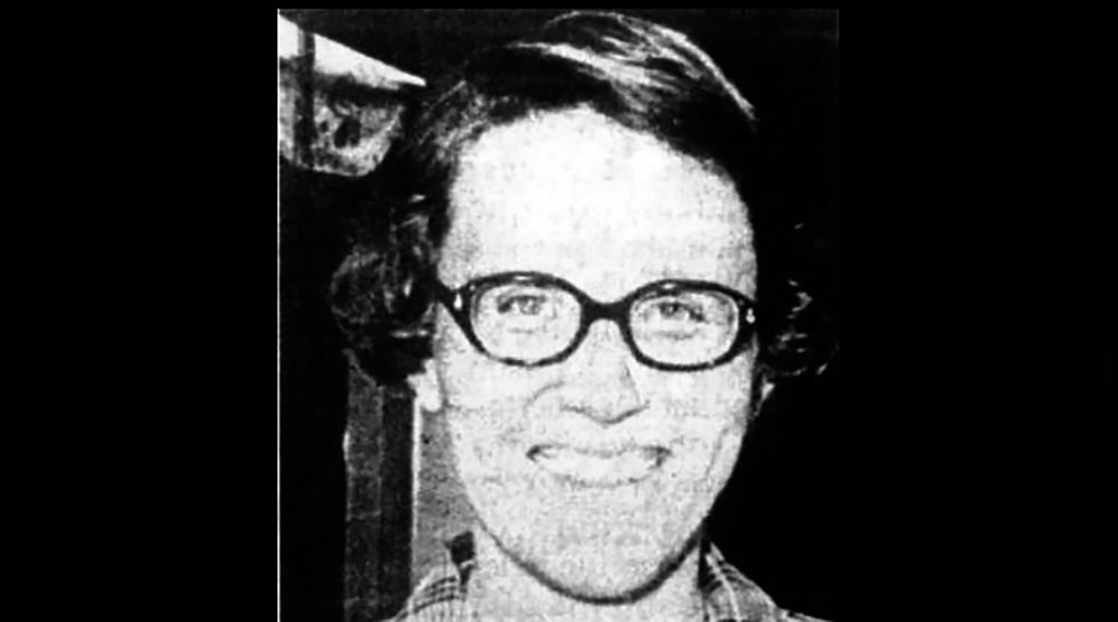 Black and white image of a smiling white woman with glasses and a checked shirt