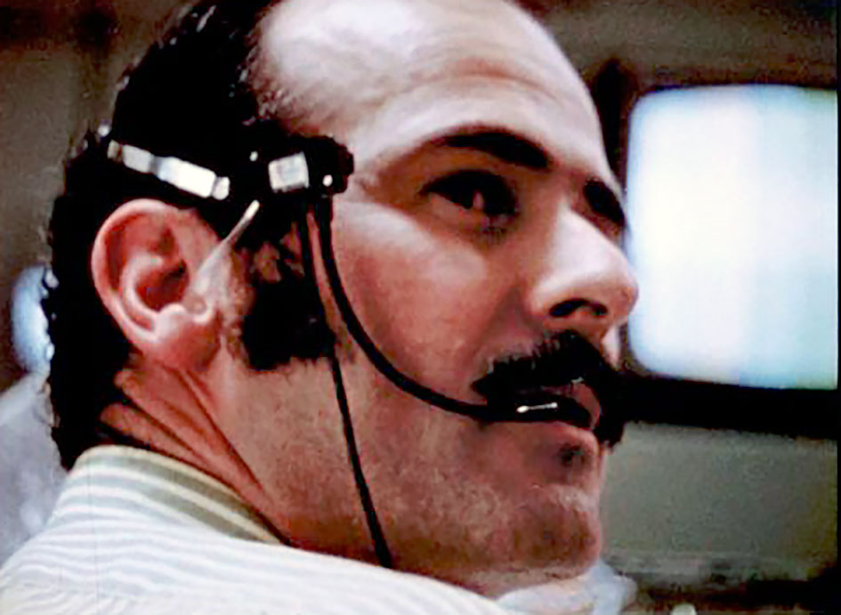 A white man with a dark moustache, wearing a headset and looking off to one side of the photo